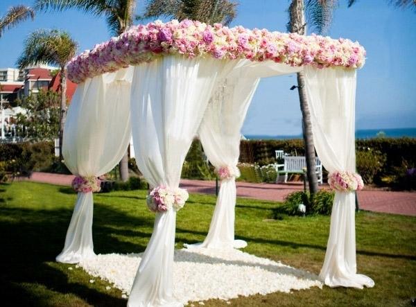 En romantisk paviljong med vit tyg och blommor